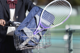 自転車のかごに入ったテニスラケットとカバンの写真素材 [FYI01304076]
