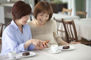 スマートフォンを見て話す中高年女性2人の写真素材 [FYI01304090]