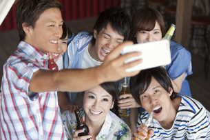 飲食店で写真を撮る男女6人の写真素材 [FYI01304095]