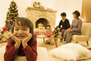 ほおづえをしている男の子と家族の写真素材 [FYI01304408]