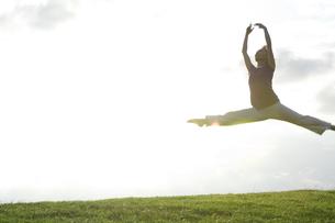 芝生の上でジャンプする女性の写真素材 [FYI01304453]