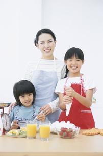 お菓子作りをする親子3人の写真素材 [FYI01304631]