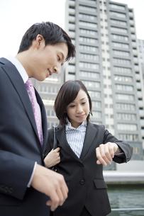 時計を見るビジネスマンとビジネスウーマンの写真素材 [FYI01304688]