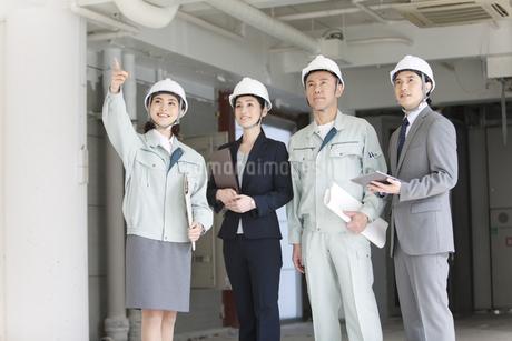 建設現場でチェックをする男女4人の写真素材 [FYI01304717]