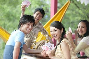 トランプで遊ぶ男女4人の写真素材 [FYI01304718]