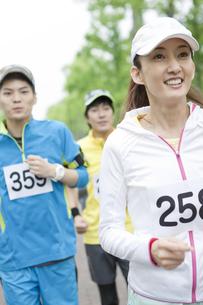 スポーツウェアを着て走る男女3人の写真素材 [FYI01304804]