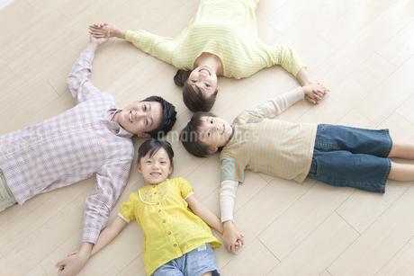 輪になって寝そべる4人家族の写真素材 [FYI01304869]