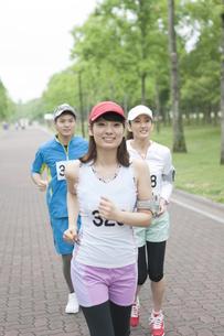 スポーツウェアを着て走る男女3人の写真素材 [FYI01304982]