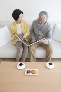 アルバムを見て話す中高年夫婦の写真素材 [FYI01305035]