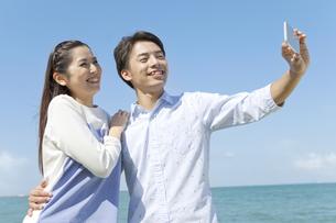 携帯電話で写真を撮るカップルの写真素材 [FYI01305104]