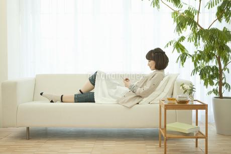 ソファーでくつろぐ女性の写真素材 [FYI01305351]