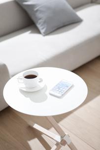 サイドテーブルの上のコーヒーとスマートフォンの写真素材 [FYI01305559]