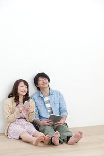 壁にもたれるカップルの写真素材 [FYI01305579]