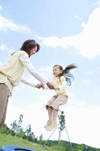 トランポリンで遊ぶ親子の写真素材 [FYI01305630]