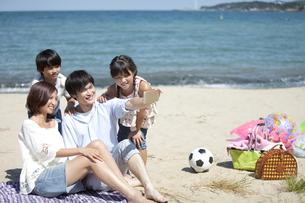 スマートフォンで撮影する4人家族の写真素材 [FYI01305704]