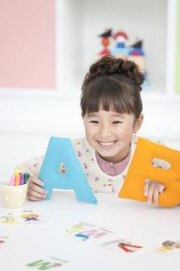 アルファベットのオブジェを持つ女の子の写真素材 [FYI01305747]