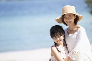 海辺に立つ笑顔の親子の写真素材 [FYI01305798]