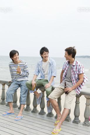 手すりに座って話す3人の男性の写真素材 [FYI01305849]