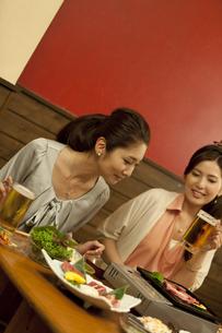 焼き肉を見ている女性2人の写真素材 [FYI01305934]