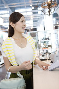 レジで支払いをする女性の写真素材 [FYI01305940]