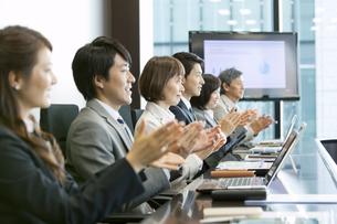 会議室で拍手をするビジネス男女の写真素材 [FYI01306022]