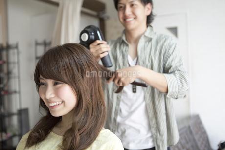 髪をブローしてもらう女性の写真素材 [FYI01306045]