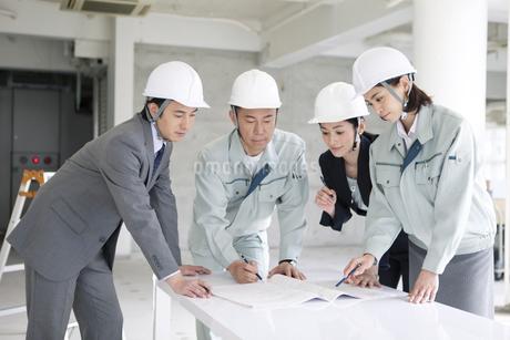 建設現場で打ち合わせをする男女4人の写真素材 [FYI01306049]