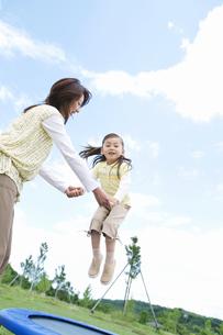 トランポリンで遊ぶ親子の写真素材 [FYI01306067]