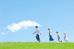 芝生を歩く4人家族の写真素材 [FYI01306088]