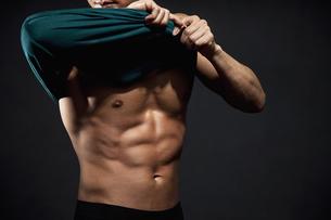 服を脱ぐ筋肉質の男性の写真素材 [FYI01306340]