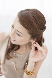 イヤリングを触っている中年女性の写真素材 [FYI01306417]