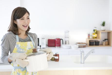 鍋を運ぶ女性の写真素材 [FYI01306535]