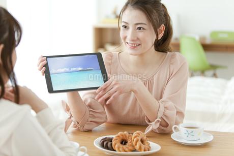 部屋でタブレットPCを見る女性2人の写真素材 [FYI01306582]