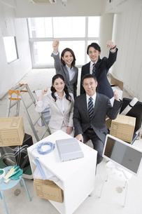 荷物に囲まれたビジネスマンとビジネスウーマン4人の写真素材 [FYI01306652]