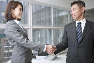 握手をするビジネスマンとビジネスウーマンの写真素材 [FYI01306695]