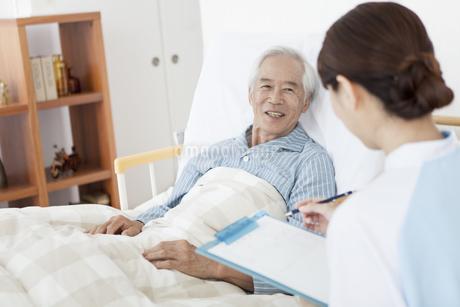 カルテを書く女性介護士とシニア男性の写真素材 [FYI01306719]