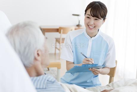 カルテを書く女性介護士とシニア男性の写真素材 [FYI01306728]