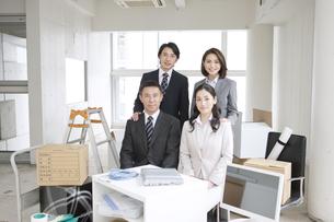 荷物に囲まれたビジネスマンとビジネスウーマン4人の写真素材 [FYI01306800]