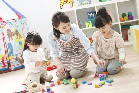 おもちゃで遊ぶ園児と保育士の写真素材 [FYI01306838]