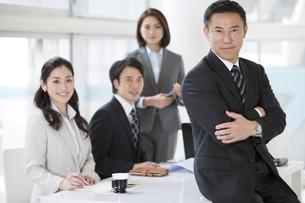 腕組みをするビジネスマンと同僚3人の写真素材 [FYI01306873]