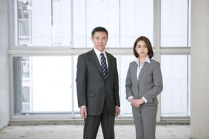 部屋に佇むビジネスマンとビジネスウーマンの写真素材 [FYI01307030]