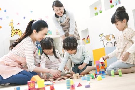 おもちゃで遊ぶ園児と保育士の写真素材 [FYI01307044]
