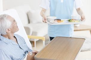 食事を運ぶ女性介護士とシニア男性の写真素材 [FYI01307109]