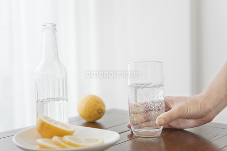 レモンと水の入ったコップを持つ手の写真素材 [FYI01307137]