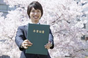 卒業証書を差し出す男子大学生の写真素材 [FYI01307189]