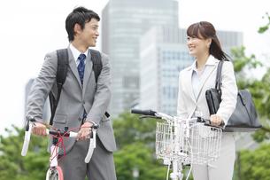 自転車を押すビジネスマンとビジネスウーマンの写真素材 [FYI01307352]