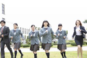 校庭を走る女子校生と先生の写真素材 [FYI01307464]