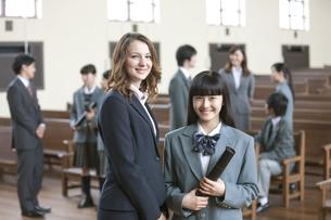 卒業証書を持つ女子校生と外国人教師の写真素材 [FYI01307496]