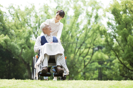 車椅子に乗るシニア男性と介護士の写真素材 [FYI01307522]