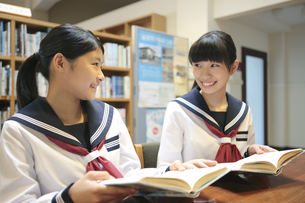 図書室で本を読む女子校生2人の写真素材 [FYI01307614]